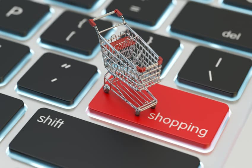 Internet shopping and online purchases concept, macro view of supermarket shopping cart on a computer keyboard